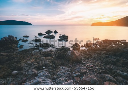 Black rock beach with smooth milky sea surface and sunset behind mountain on cloudy sky.