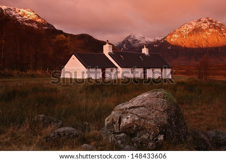 Black Rock Cottage, Rannoch Moor, nr Glencoe, Scottish Highlands. The mountain peaks are bathed in the warm glow of sunrise in Autumn. Horizontal orientation. - stock photo