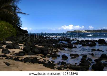 Black rocks fill beach in Hanalei Bay on Kauai, Hawaii.  Deep aqua blue water with vivid blue sky. - stock photo