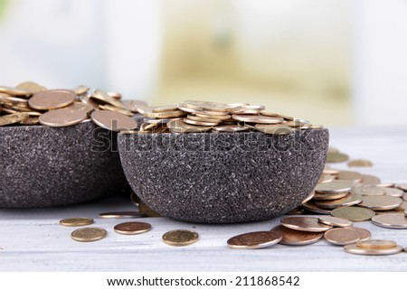 Black round plates full of Ukrainian coins on wooden table - stock photo