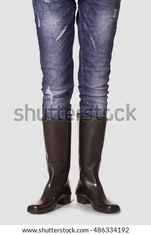 Black rubber boots on grey background.
