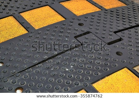 Black rubber speed bump with yellow reflectors close-up - stock photo