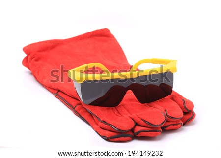 Black safety glasses with red leather gloves isolated on white background - stock photo
