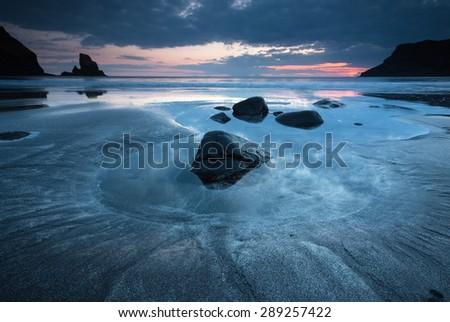 Black sands at Talisker Bay at sunset. - stock photo