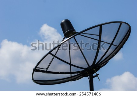 Black satellite dish in blue sky with clouds. - stock photo
