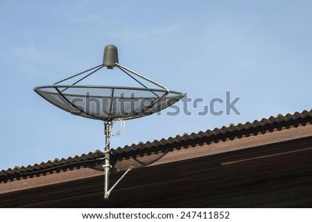 black satellite disk on roof of house in sunlight - stock photo