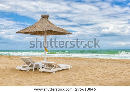 Black Sea beach with umbrellas, fine sand, cool water and blue cloudy sky. - stock photo