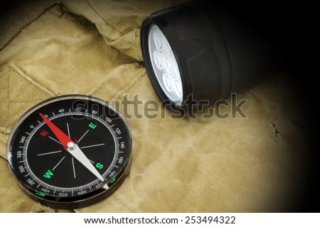Black Searchlight, compass and  handcuffs On Weathered Handbag. Camouflage Army Textured Background. - stock photo