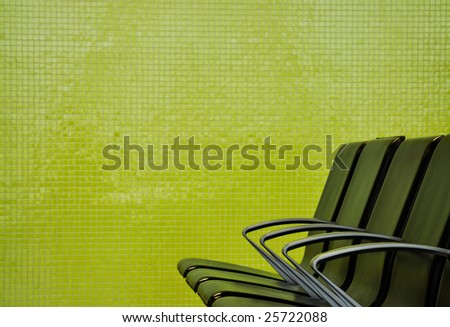 black seats in front of a tiled wall - stock photo