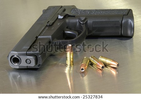 Black semi-automatic handgun with bullets, high depth of field - stock photo
