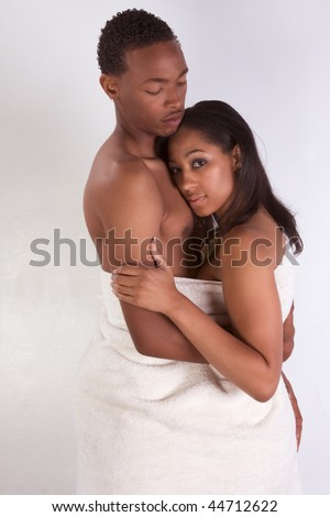 Black sensual couple, African American man and woman of Creole ethnicity hugging wrapped in bathtowel - stock photo