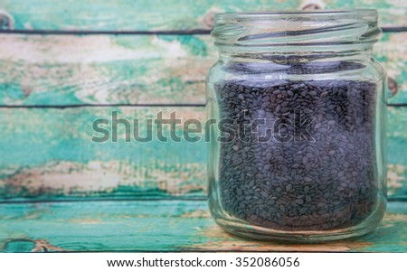 Black sesame seed in mason jar over wooden background - stock photo
