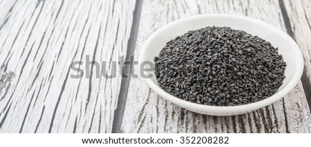 Black sesame seed in white bowl over wooden background - stock photo