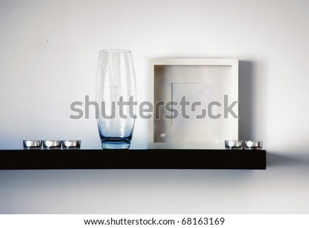 black shelf with vase,frame and candles - stock photo