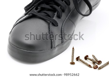 Black shoe and  metal nails. - stock photo