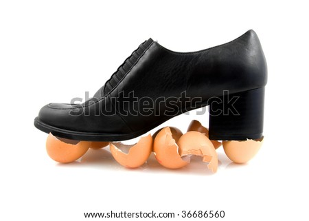 black shoe on egg shells; walking on eggs, isolated on white background - stock photo