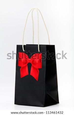 Black shopping bag with red bow  on white - stock photo