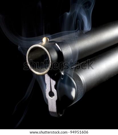 Black shotgun that has smoke coming from around its barrel - stock photo