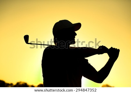 Black silhouette close-up of male golf player with hat teeing-off at beautiful golf course. Professional golf player smiling. - stock photo