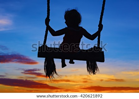 Black silhouette of baby girl flying high with fun on rope swing on blue orange sunset sky background. Travel lifestyle, people beach activity on summer family vacation with child in tropical island. - stock photo