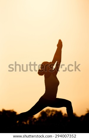 Black  silhouette of yogi girl in low lunge pose. Beautiful woman practicing outdoors in the evening against sunset sky. - stock photo
