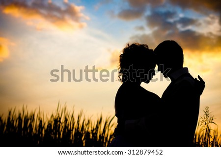 Black silhouettes of men and women against the background of a beautiful sunset, love, dating, kiss - stock photo