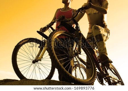 black silhouettes of young adult activity Couple friends in shirt of two bicyclists on brink rock looks at yellow summer sunset sky background in love ride bicycles along beach horizon  No face  - stock photo