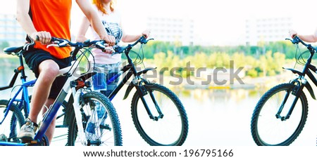 black silhouettes of young adult activity Couple friends in shirt of two bicyclists on brink rock looks at blue summer sunset sky background in love ride bicycles along beach horizon No face - stock photo