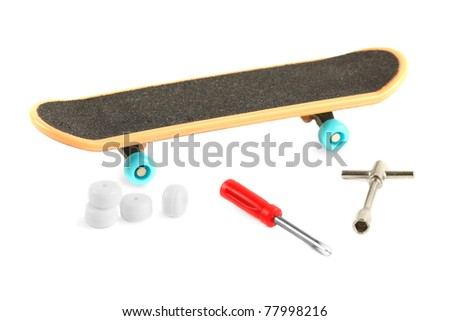 Black skateboard with yellow edge and blue wheel near tools and additional white wheels