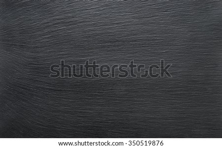 Black slate background or textured stony table close-up