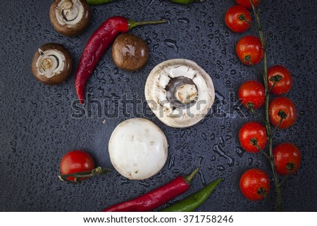 black slate with cucumbers, peppers and tomatoes and mushrooms