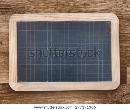black slate with grid-lines on wooden background