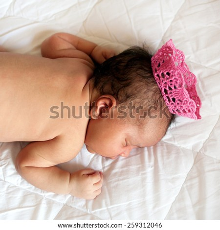 Black small newborn baby sleeping on a bed in a crown, closeup.  - stock photo