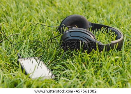 Black Smartphone and Headphones on the Green Grass