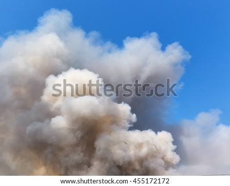 Black smoke cloud on the blue sky (select focus) - stock photo
