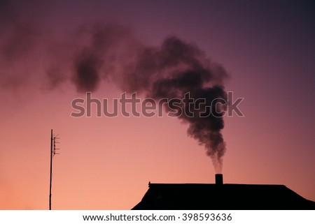 Black smoke comes out of a house's chimney in dusk.  - stock photo