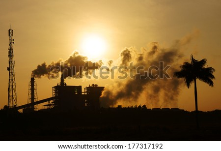 Black smoke from smoke stack of factory in industrial zone rose in to the air, it make polluted enviroment, the plant and tree in silhouette at sunrise, atmosphere cover with waste exhaust - stock photo