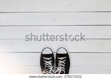 Black sneakers with laces on a white wooden floor. top view - stock photo