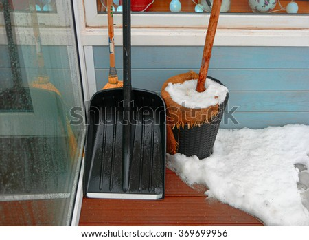 Black snow shovel standing in the snow leaning cafe wall. - stock photo