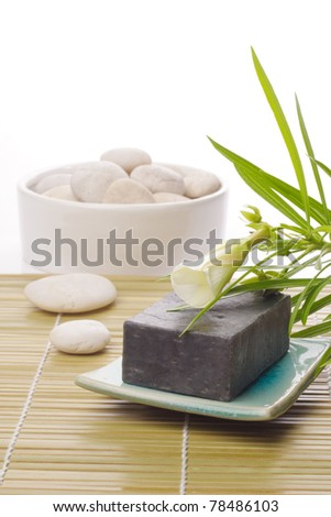 black soap, white flower and white stone on bamboo mat - stock photo