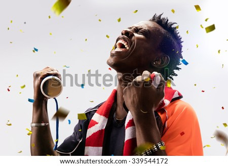 black Soccer fan in action emotions confetti - stock photo