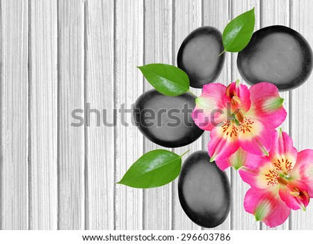 Black spa stones and pink orchid on white wooden background - stock photo