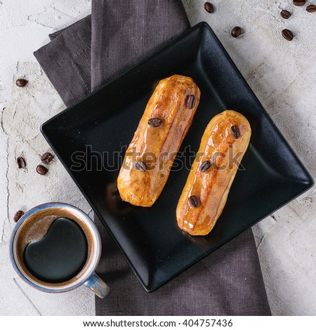 Black square plate with Coffe eclairs with cup of fresh black coffee and coffee beans on gray textile napkin over plastered surface.  Top view. Square image - stock photo