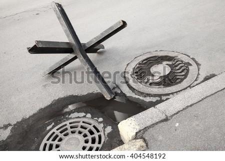 Black steel street barrier in shape of anti-tank Czech hedgehog obstacle defense stands on asphalt urban road near sewer manholes - stock photo