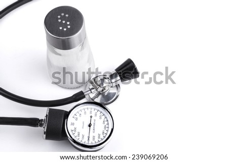 Black stethoscope and sphygmamanometer with salt in the background isolated on white - stock photo
