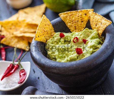 black stone bowl with fresh guacamole and nachos for dip - stock photo