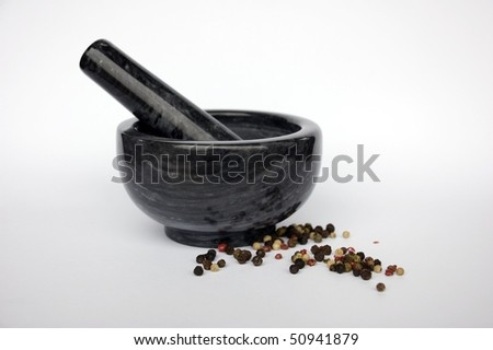 Black stone mortar and pestle over white background with colorful pepper around - stock photo