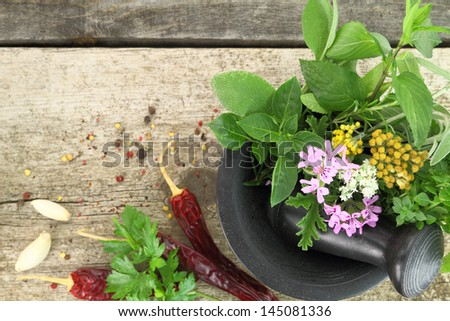Black stone mortar and pestle with fresh herbs on old wooden background - stock photo