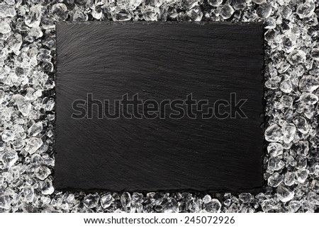 Black stone plate on ice top view - stock photo