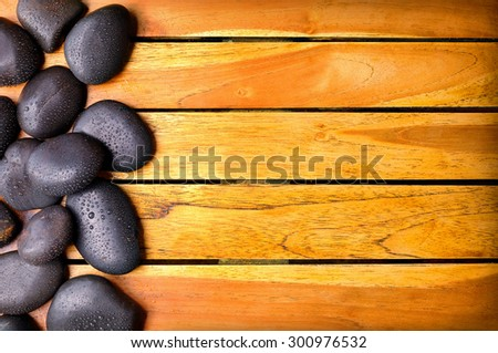 Black stones with water drops on the left side on wooden slats. Sauna and massage concept. Horizontal composition. Top view - stock photo